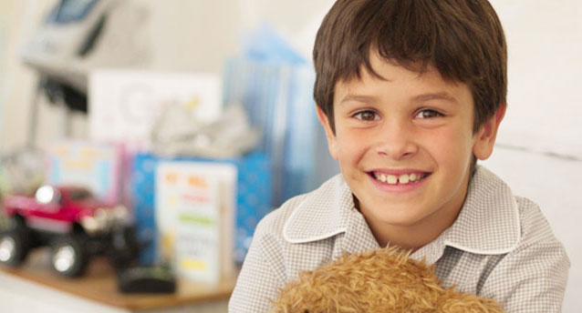 cute little boy with gaps in his teeth smiling and holding a teddy bear